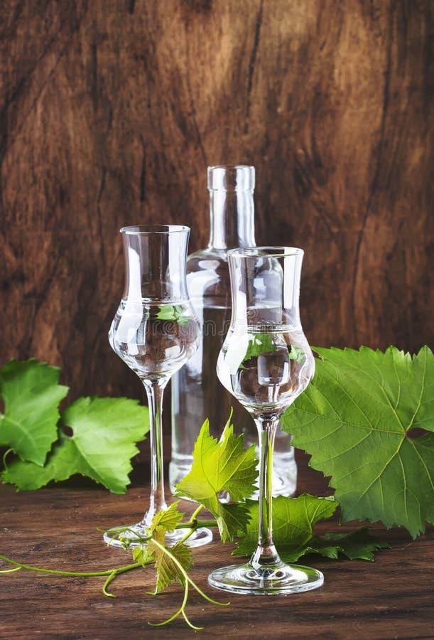 Vodca da uva, pisco - bebida alcoólica forte peruana tradicional em vidros elegantes na tabela de madeira do vintage, espaço da c fotografia de stock