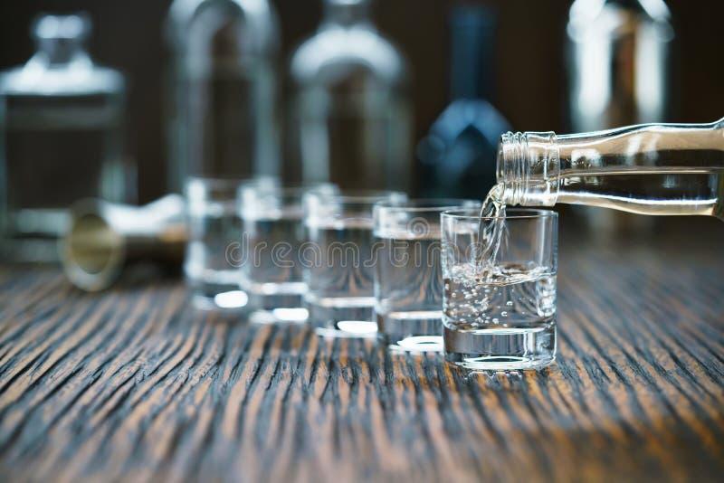 Vodca que derrama da garrafa no vidro em uma barra, FO seletivas fotos de stock royalty free