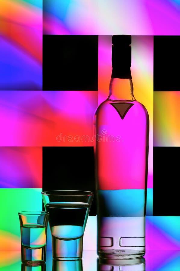 Vodka bottle and shot glasses stock photos
