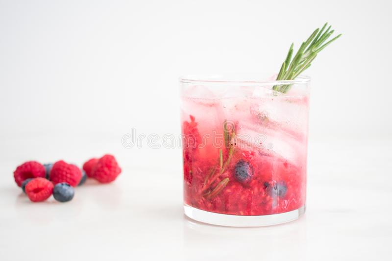 Berry and Rosemary Vodka Cocktail on the Rocks. A vodka cocktail made with blueberries, raspberries, and rosemary served in a rocks glass royalty free stock images