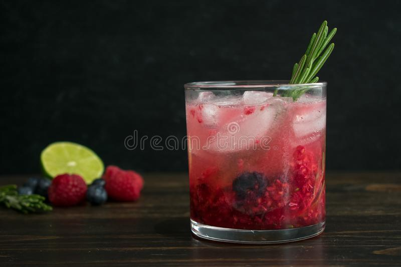 Berry and Rosemary Vodka Cocktail on the Rocks. A vodka cocktail made with blueberries, raspberries, and rosemary served in a rocks glass royalty free stock image