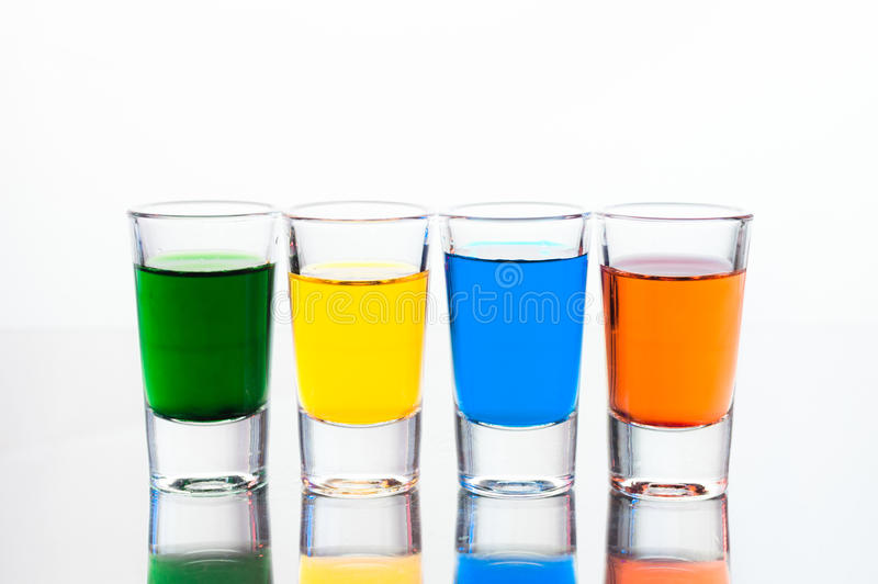 Vodka color shots filled with alcohol on glass bar table royalty free stock images