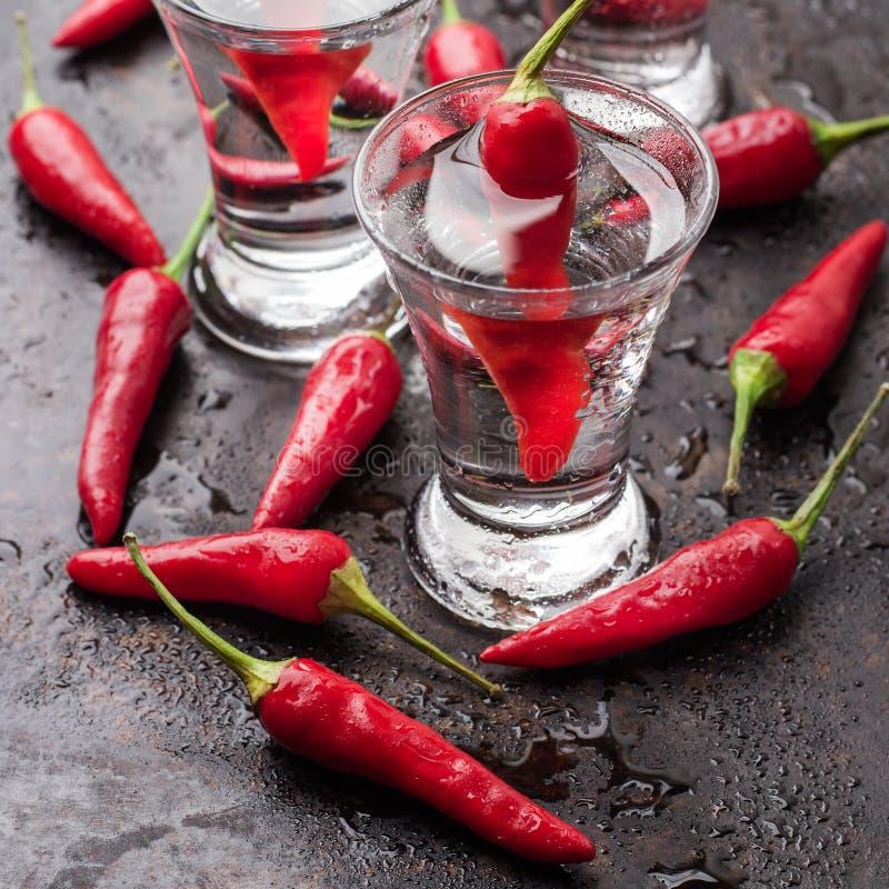 Vodka con pimientas de chile en la tabla oxidada del grunge imagen de archivo
