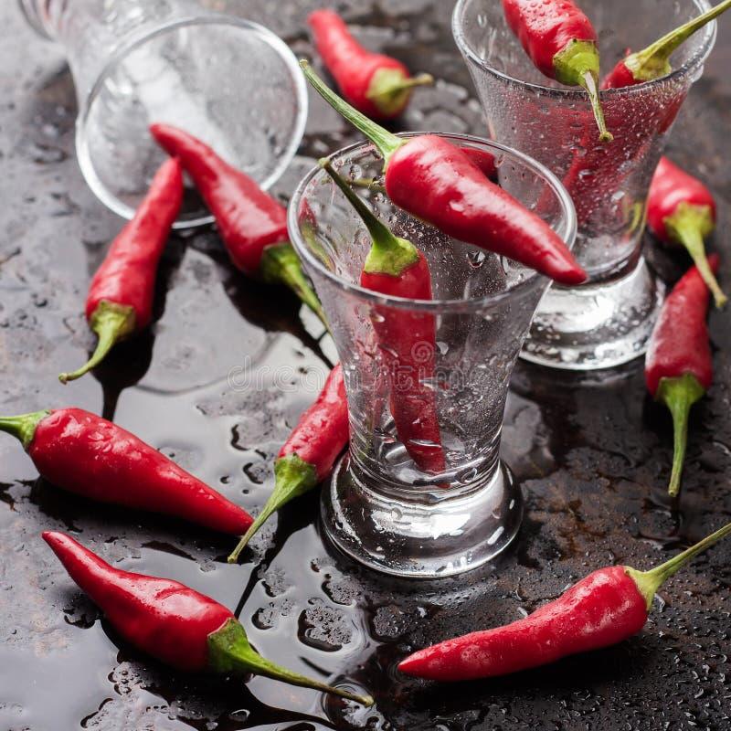 Vodka con pimientas de chile en la tabla oxidada del grunge fotografía de archivo libre de regalías
