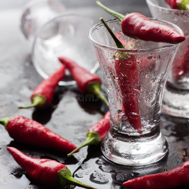 Vodka con pimientas de chile en la tabla oxidada del grunge imagen de archivo libre de regalías