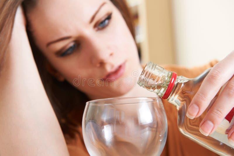 Vodka de versement de jeune femme malheureuse dans le verre images stock
