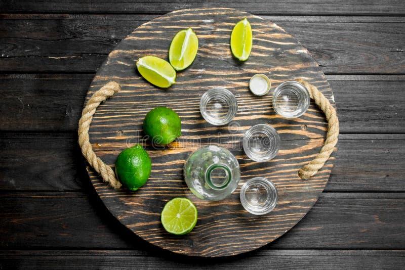 Vodka i ett skjutit exponeringsglas och en flaska på magasinet med limefrukt arkivbilder