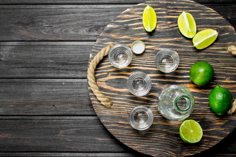 Vodka i ett skjutit exponeringsglas och en flaska på magasinet med limefrukt royaltyfria bilder