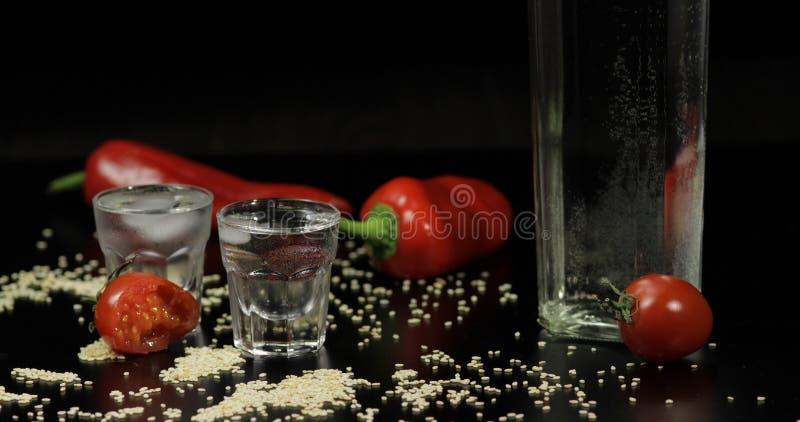 Vodka i sköt exponeringsglas som förläggas på en svart yttersida fotografering för bildbyråer