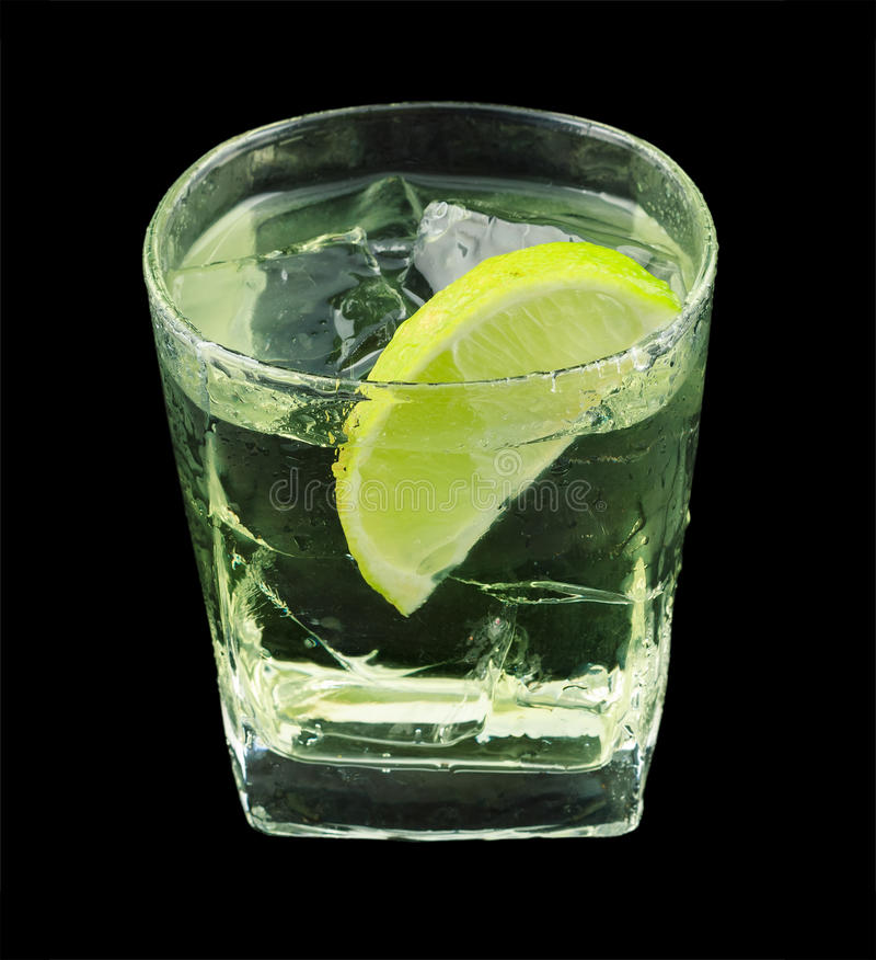 Vodka lime cocktail. Vodka lime is a cocktail that contains vodka, lime cordial and is garnished with a lime wedge. Isolated on black stock photo