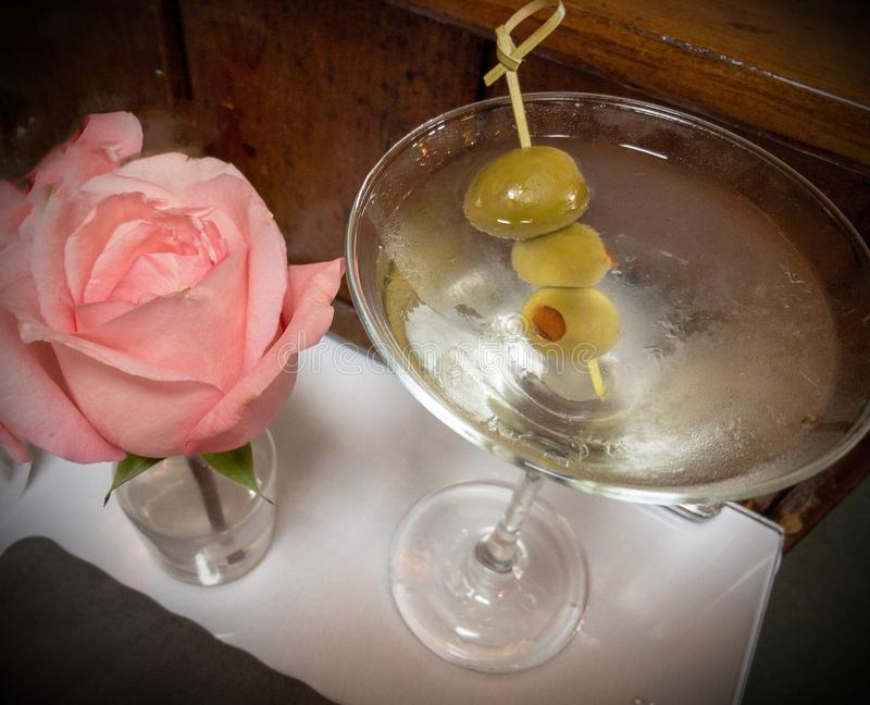 Vodka Martini with olives next to a pink rose. stock image