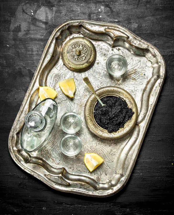 Vodka med kaviaren på det gamla magasinet royaltyfri bild