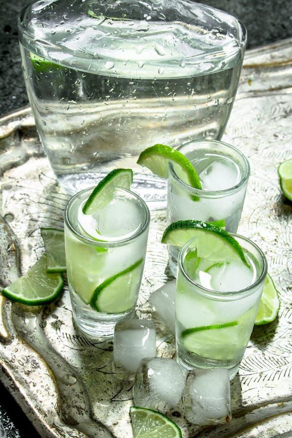 Vodka med limefrukt och is på ett stålmagasin arkivfoton