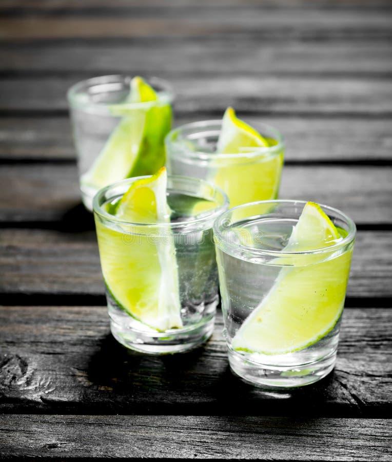 Vodka med limefruktskivor i ett skjutit exponeringsglas arkivfoton