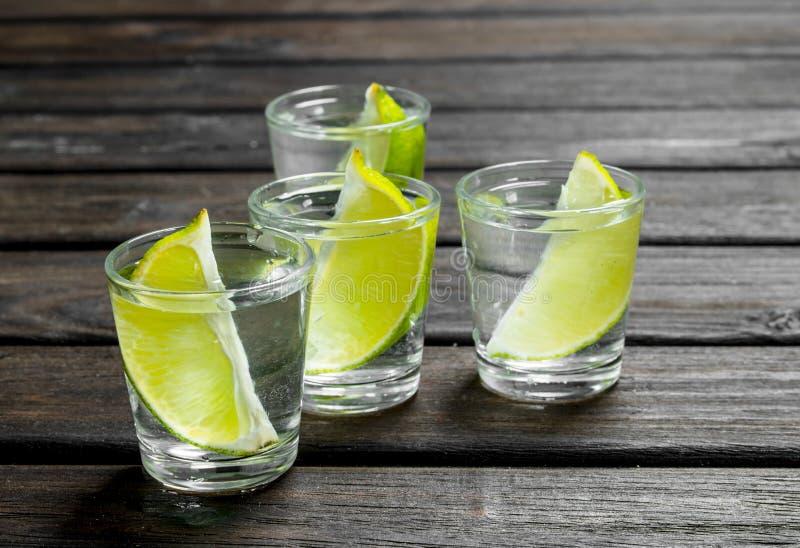 Vodka med limefruktskivor i ett skjutit exponeringsglas royaltyfri foto