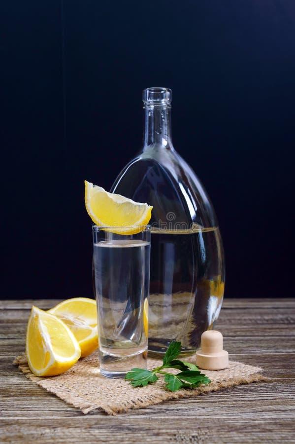 Vodka o tequila en vasos de medida y en la botella con el  e del sliÑ del limón en fondo de madera rústico fotografía de archivo libre de regalías