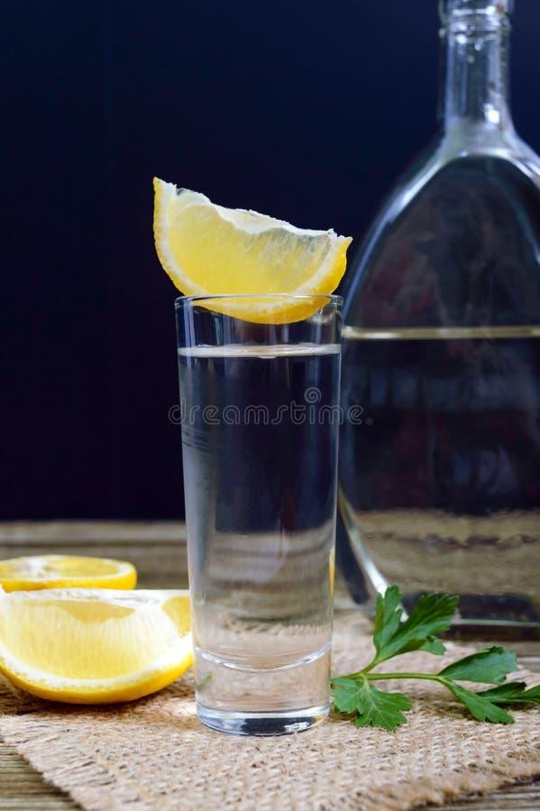 Vodka o tequila en vasos de medida y en la botella con el  e del sliÑ del limón en fondo de madera rústico imagenes de archivo