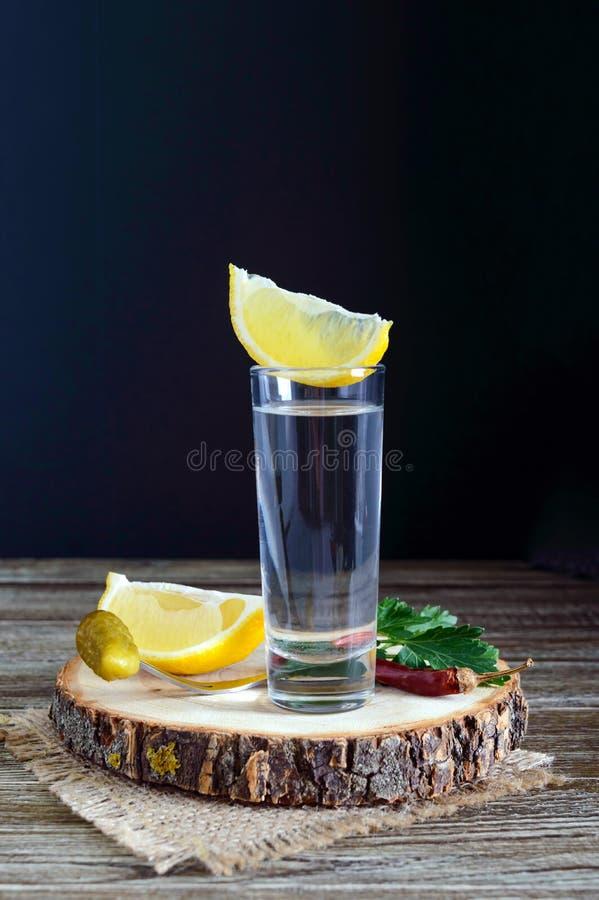 Vodka o tequila en vasos de medida y en la botella con el  e del sliÑ del limón en fondo de madera rústico imágenes de archivo libres de regalías