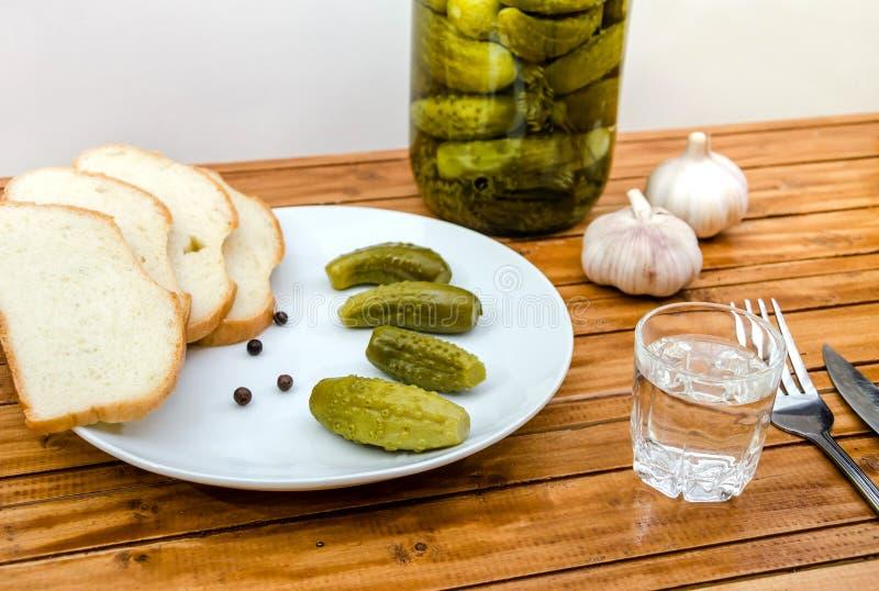 Vodka, pepinos conservados en vinagre, pan y ajo en una tabla de madera fotos de archivo