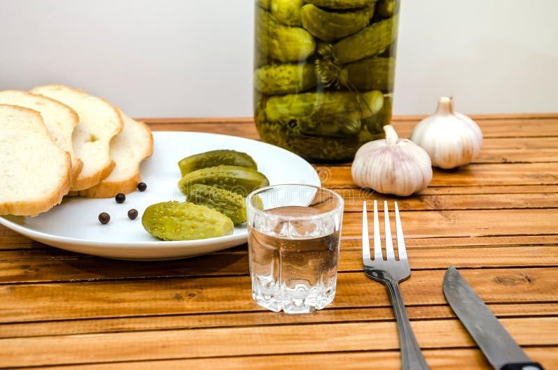 Vodka, pepinos conservados en vinagre, pan y ajo en una tabla de madera imágenes de archivo libres de regalías