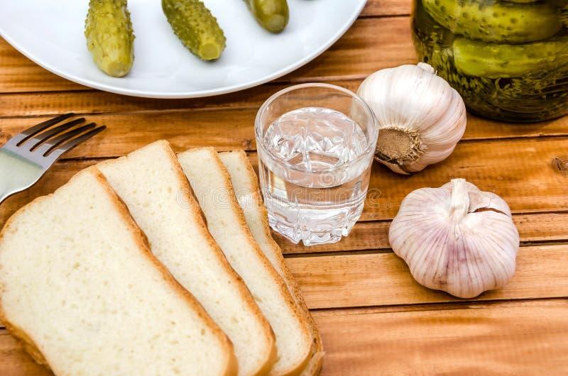 Vodka, pepinos conservados en vinagre, pan y ajo en una tabla de madera fotografía de archivo libre de regalías