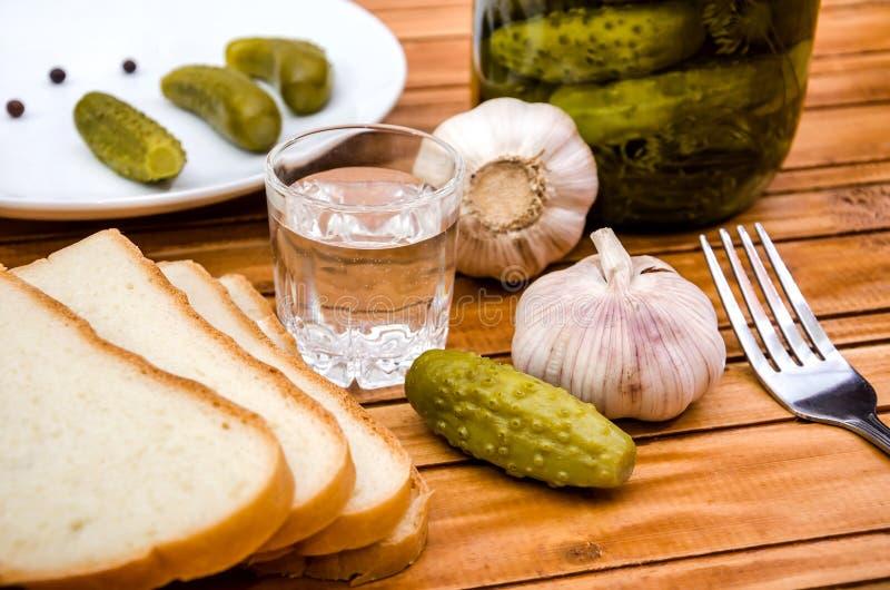 Vodka, pepinos conservados en vinagre, pan y ajo en una tabla de madera foto de archivo libre de regalías