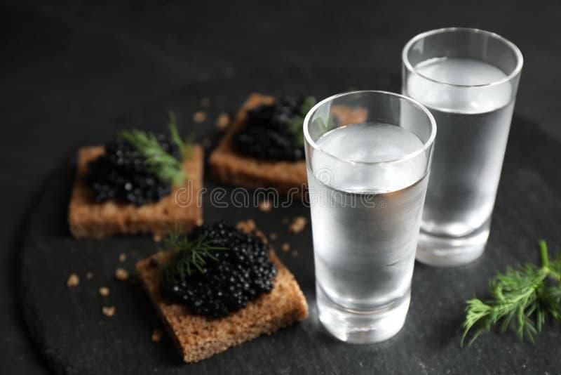 Vodka russa fredda e panini con caviale nero sul tavolo fotografie stock