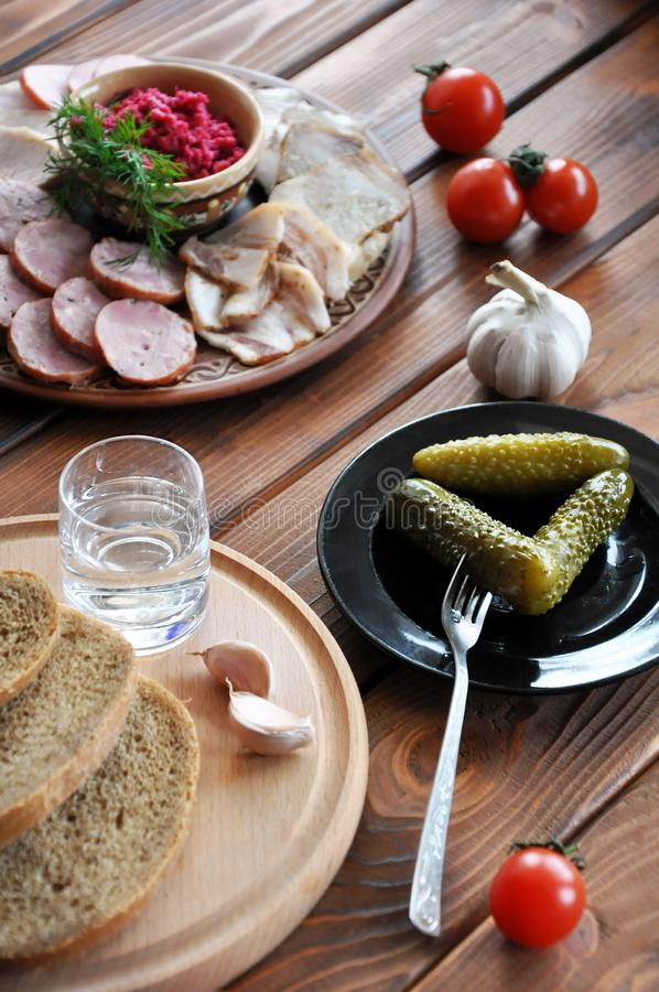 Vodka with salted cucumbers, rye bread and lard stock photography