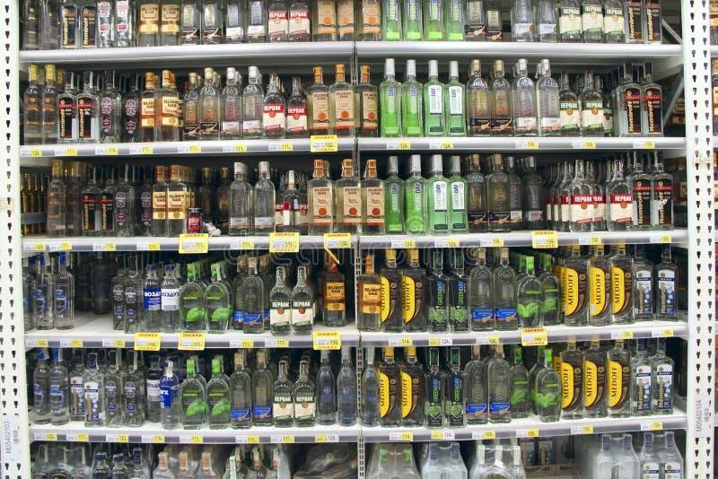 Vodka shoppar med bred choise Alkoholdrycker på hyllor av supermarket royaltyfri bild