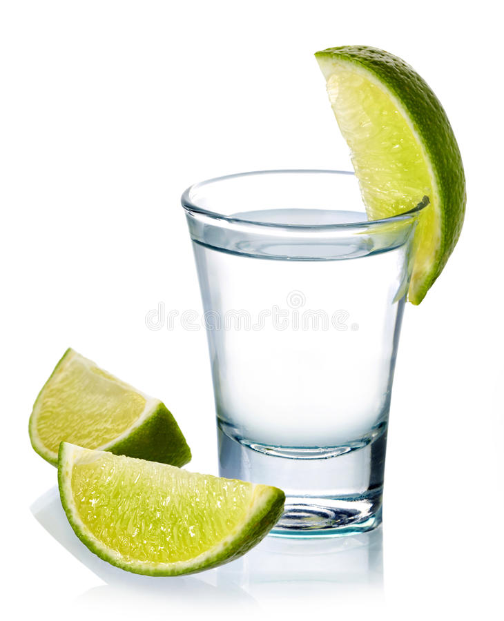 Vodka shot. Glass of vodka shot with fresh lime isolated on white background royalty free stock photos