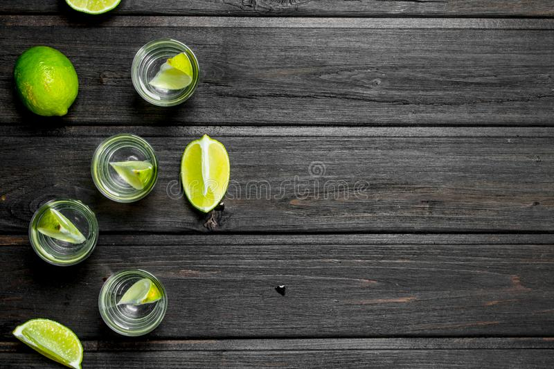 Vodka in a shot glass and lime slices. On wooden background stock photography