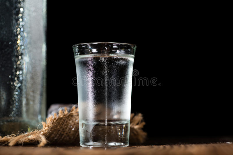 Vodka Shot. With ice on an old rustic wooden table stock photography