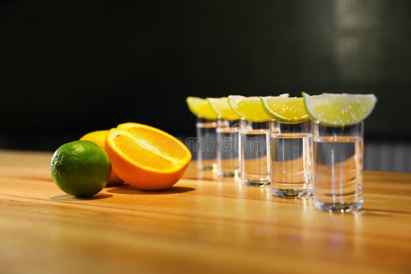 Vodka shots and citrus fruits on bar counter royalty free stock image