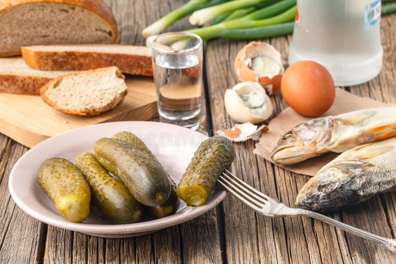 Vodka with traditional Slavonic snacks on table - hering, pickl stock photography