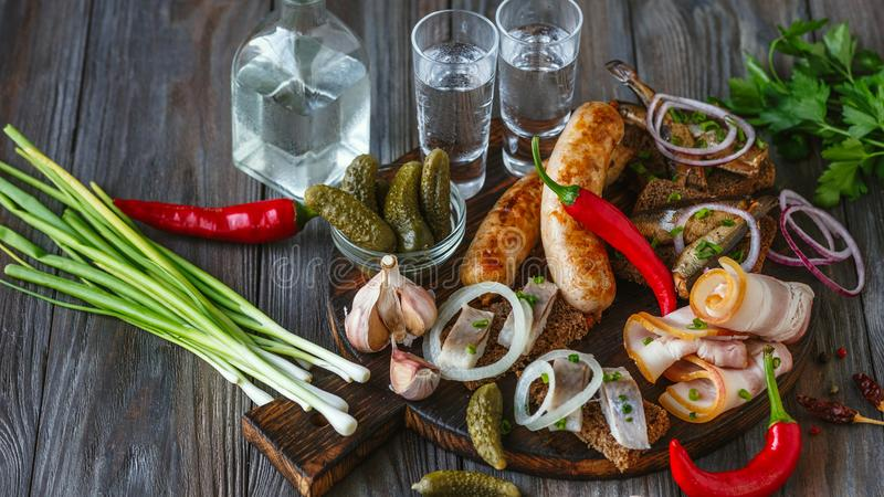 Vodka and traditional snack on wooden background. Vodka with lard, salted fish and vegetables, sausages on wooden background. Alcohol pure craft drink and royalty free stock image