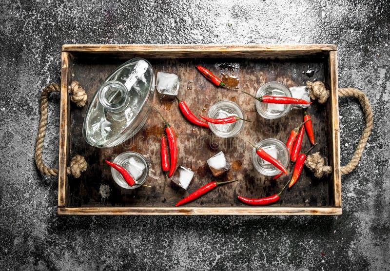 Vodkaskott med chilipeppar på ett trämagasin fotografering för bildbyråer