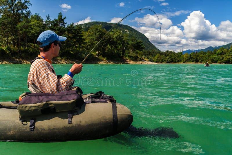 Voe o pescador no bellyboat que luta com truta grande, Eslovênia foto de stock