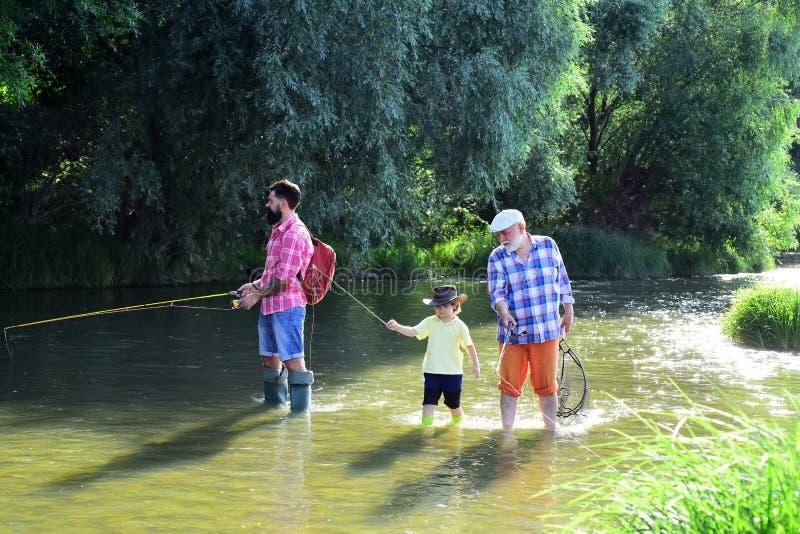Voe o pescador que usa a haste de pesca com mosca no rio O vovô e o neto são pesca com mosca no rio Bisavô e grande fotografia de stock royalty free
