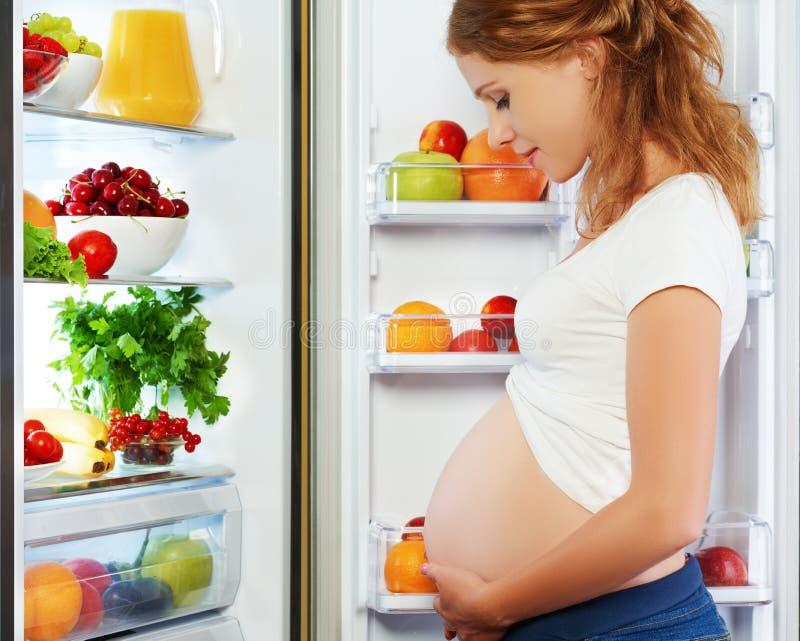 Voeding en dieet tijdens zwangerschap Zwangere vrouw met vruchten stock afbeeldingen