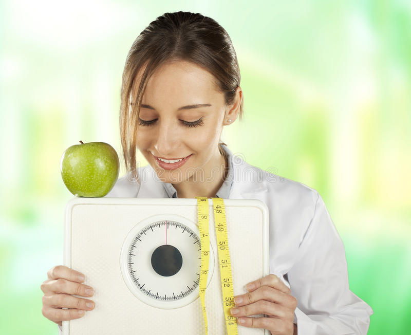 Voedingsdeskundige die en op een gewichtsschaal en op een groene appel let houdt royalty-vrije stock foto