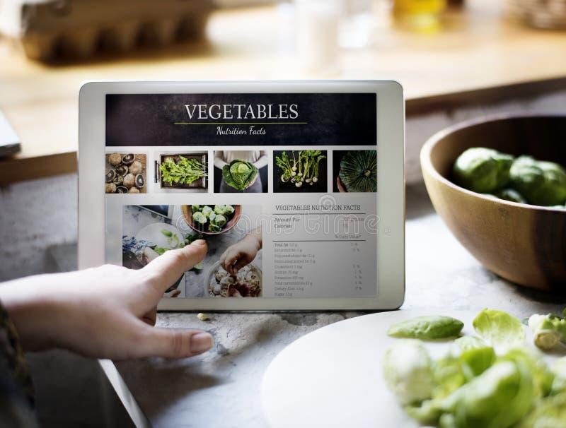 Voedingsfeiten van verse groente op digitale tablet stock fotografie