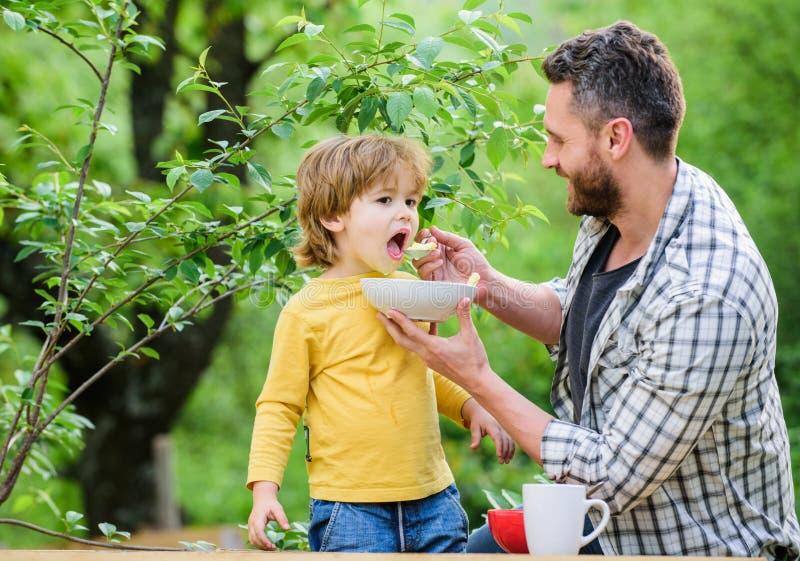 Voedingsgewoonten Weinig jongen en papa het eten Voeding voor jonge geitjes en volwassenen Gezond voedingsconcept Voedende gelukk stock afbeeldingen