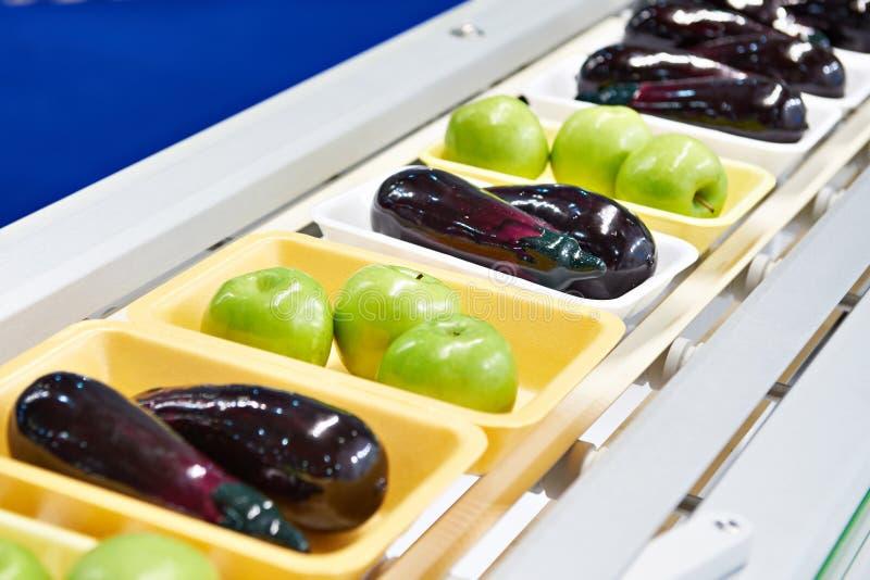 Voedingsmiddelenappelen en aubergine in plastic pak op transportband stock foto