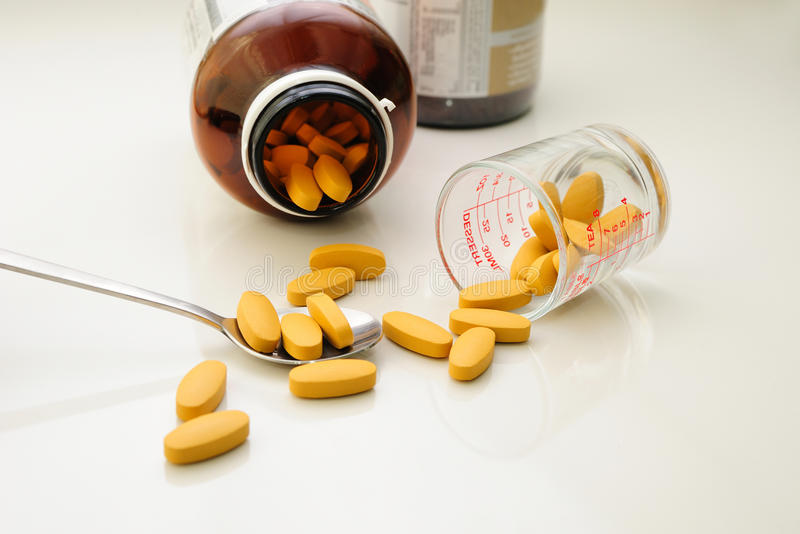 Voedingssupplement (pillen) in lepel en containers stock foto