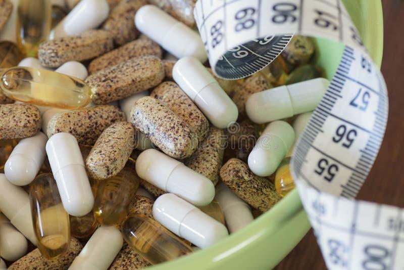 Voedingssupplementen in capsules en tabletten, op houten achtergrond stock foto