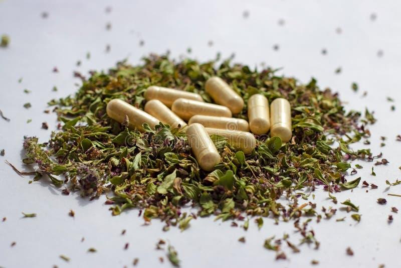 Voedingssupplementenpillen en capsules op droge kruidenachtergrond Alternatieve kruidengeneeskunde, naturopathy en homeopathie stock fotografie