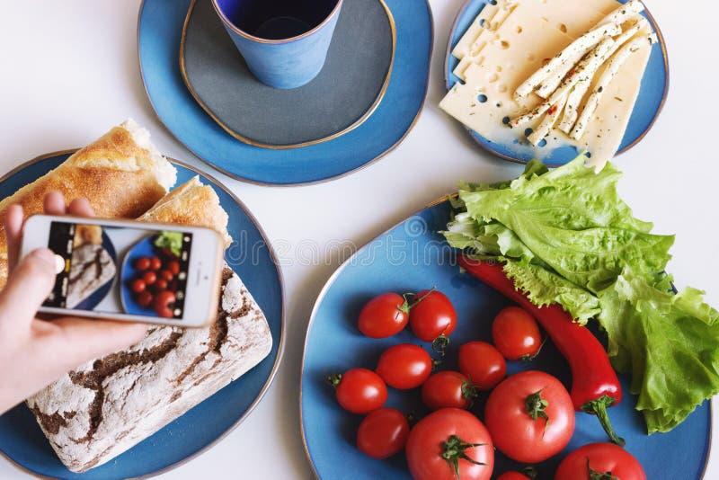 Voedsel in blauwe ontwerperschotels op lichte achtergrond Mensen` s hand die foto in telefoon nemen royalty-vrije stock fotografie