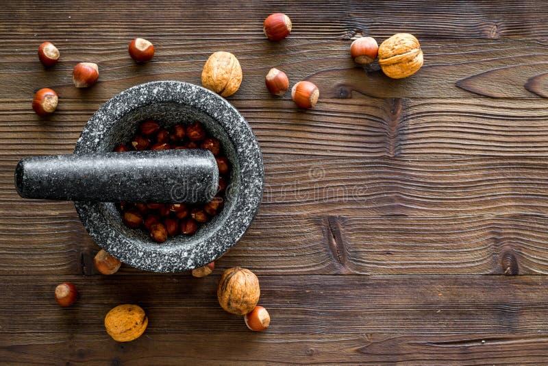 Voedsel dat met diverse noten voor het maken van tot kruiden en mortier wordt geplaatst houten achtergrond hoogste meningsmodel stock foto