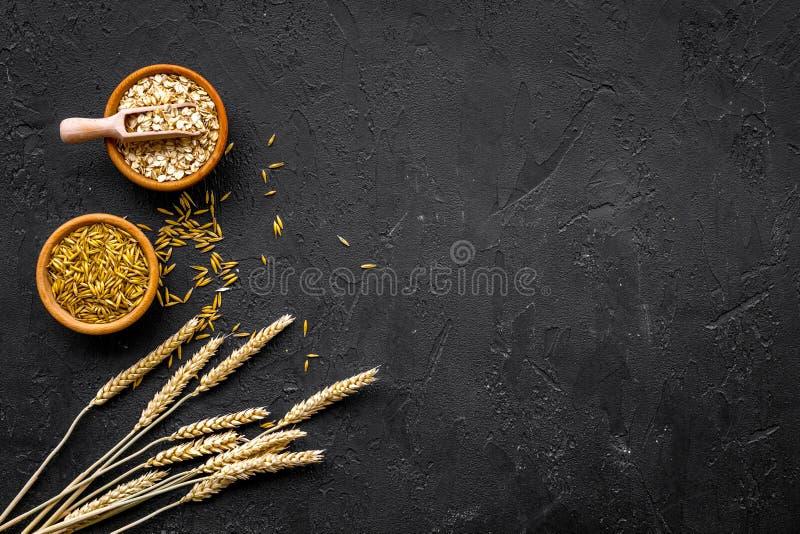 Voedsel dat rijken met langzame koolhydraten Havermeel en haver in kommen dichtbij twijgen van tarwe op zwart achtergrond hoogste stock fotografie