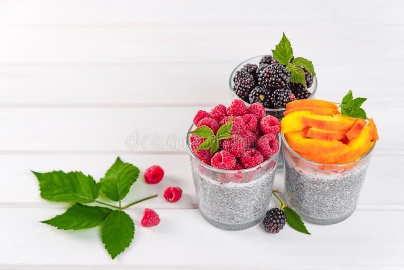 Voedsel en drank, het gezond eten en het op dieet zijn concept Eigengemaakte witte chiapudding met verse bessen en groene bladere royalty-vrije stock afbeeldingen